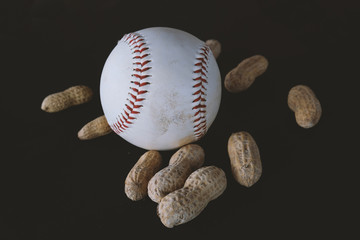 White baseball with ballpark peanuts against black background.  Ball equipment for sports graphic.