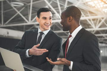Two smiling men standing in hangar and talking to each other. One of them holding laptop