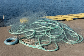 Green fishing net at the harbor with blue sea in the background