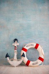 A composition on a sea theme with an anchor and lifebuoy on a blue wall