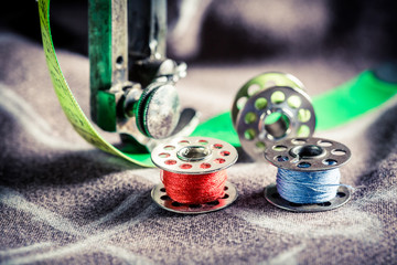 Closeup of sewing machine and colorful threads on clothes