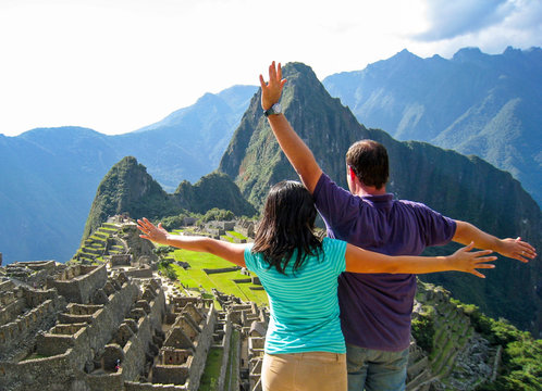 a couple raising their arms in machu picchu expressing a feeling of freedom