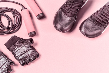 Sport fitness layout with sport shoes, jump rope, ragged gloves on pink background with blank space in the center.