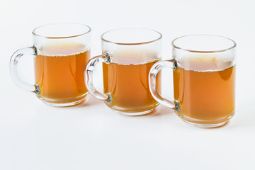 Three glass cups full of hot green tea drink on white background.