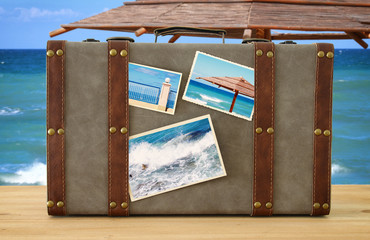 Image of old vintage luggage with vacation photos over sea tropical landscape.