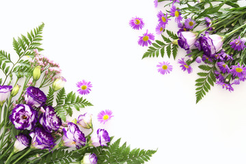Top view of purple beautiful flowers arrangement on white wooden background. Copy space.