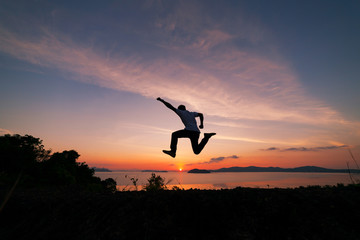 Asian man traveler is jumping on top of a rainforest mountain in scenery sunrise or sunset time background.