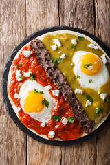 Mexican fried huevos divorciados eggs with salsa verde and roja, cheese, black beans on a tortilla close-up. Vertical top view