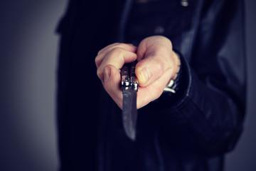 man in black leather jacket showing butterfly knife