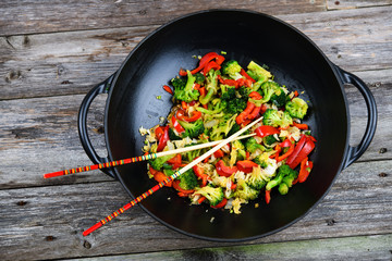 wok with vegetables and chopsticks on wooden ground