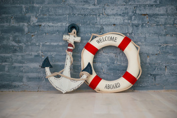 A composition on a sea theme with an anchor and life ring on a gray brick wall.