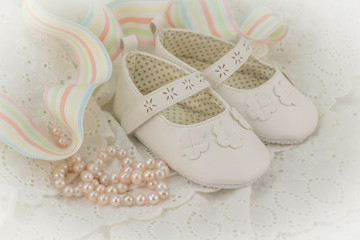 Baptism or birthday invitation background for baby girl with pink pearls, white shoes and ribbon on lace dress