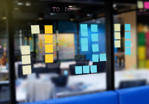 Colorful post it on glass wall at meeting room with marker and sticky notes for people share ideas, Business Meeting and Planning Concept.