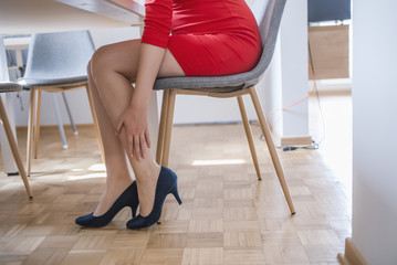 Woman sitting a feeling pain Ankle sprain or Ankle leg pain or Leg pain. Image of a woman suffering from pain in ankle while walk on high heels. healthcare ,lifestyle