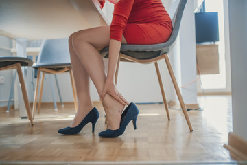 closeup of elegant young office worker lady wearing high heel shoes long time feeling ankle pain uncomfortable and sitting on wood floor seat chair waiting for interview.