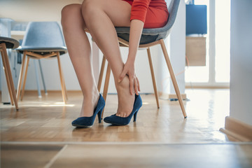 Young woman with slim legs feeling ache because of wearing high heels
