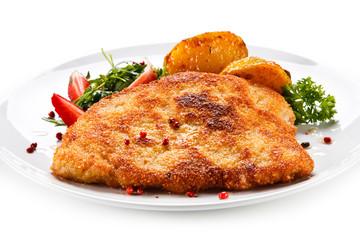 Fried pork chop, baked potatoes and vegetable salad