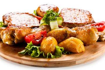 Grilled steak and drumsticks with potatoes on cutting board
