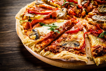 Pizza with ham and vegetables on wooden table