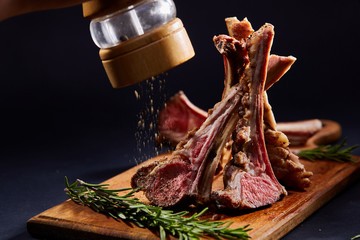 Rack of lamb with rosemary on wooden cutting board over dark background, side view, selective focus