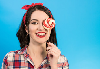 The happy woman with a candy gesturing on the blue background