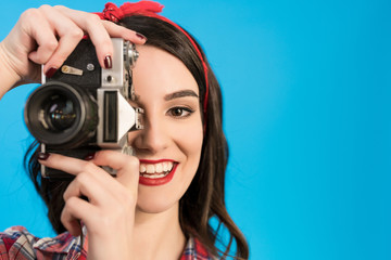 The happy girl takes a photo with an retro camera on the blue background
