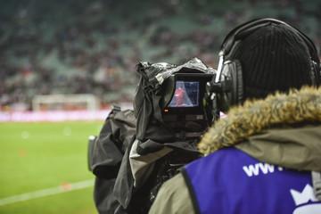 TV camera during football match.