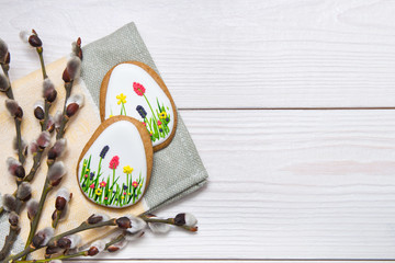 Easter gingerbread set and willow twig on white wooden background.  Easter  eggs  gingerbread