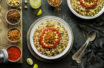 Arabic cuisine; Traditional Egyptian food:Delicious Kushary or Koushari of rice,pasta,chickpeas,lentils,crispy fried onions,fresh lemon and tomato garlic sauce on a plate.Top view with close-up
