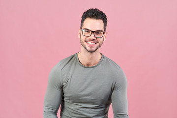 A handsome man of athletic build in glasses with a wide smile looks at the camera on an isolated pink background.