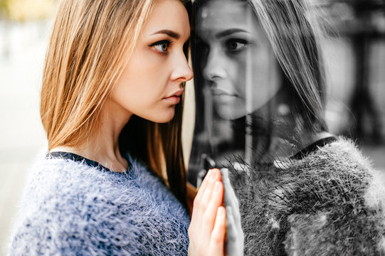 Self reflection portrait of amazing young girl in mirrored window. Unusual strange pretty woman person with sensual face looking at herself in showcase. Alter ego. Female state of mind. Other myself.