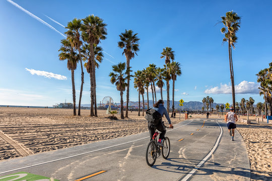 Men biking and running on Santa Monica bike path