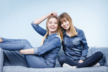 Two happy women friends wearing jeans outfit