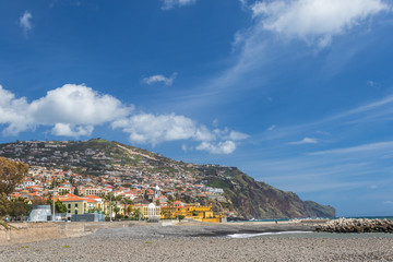 Water landscape with colorful houses on the hill and pier with the beacon on the Atlantic Ocean under the blou sky with white clouds. Funchal Madeira, the eternal spring island on a sunny day.