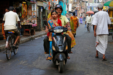 A man carries his daughter, dressed as Kumari, on a scooter, as they arrive to attend rituals to celebrate the Navratri Festival, on a road outside the Adyapeath Temple, on the outskirts of Kolkata