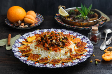 Iranian wedding pilaf topped with nuts, orange zest and raisins, rustic style