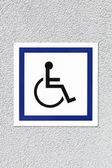 Handicap or wheelchair person symbol on a wall