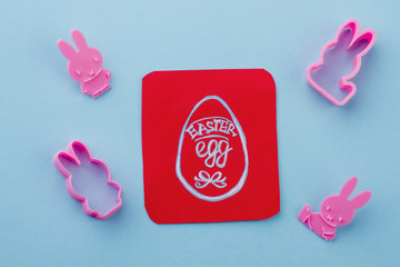 Set of animal shaped silicone forms. Easter egg drawn on red paper. Symbol of Easter holidays.