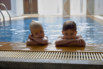 Two cute brothers preschool age, wet blonde hair, at the pool edge. Looking into camera