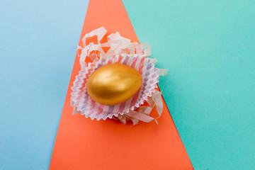 Golden egg on colorful background. Golden chicken Easter egg in paper wrap. Symbol of happy Easter.