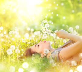 Beautiful young woman lying on the field in green grass and blowing dandelion. Healthy smiling girl on spring lawn. Allergy free concept
