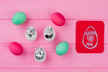 Dyed eggs and eggs with drawing faces. Easter eggs and paper card on pink wood. Easter holidays craft.