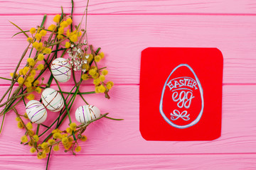 Creative Easter spring design. Styrofoam decorated Easter eggs, pussy-willow twigs and artificial grass. Picture of Easter eggs on red paper card.