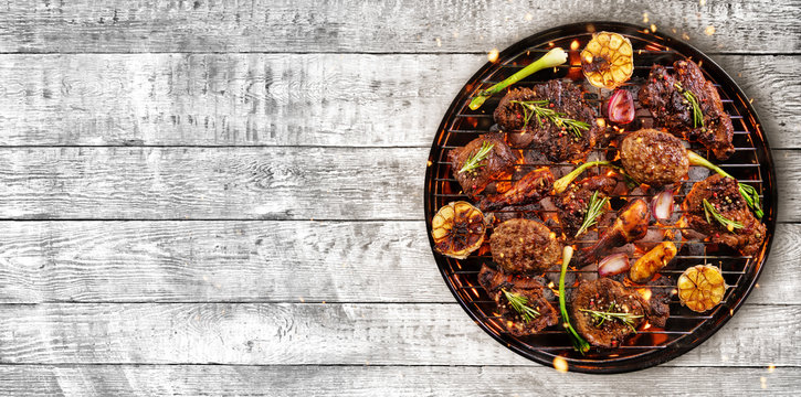 Top view of fresh meat and vegetable on grill placed on wood
