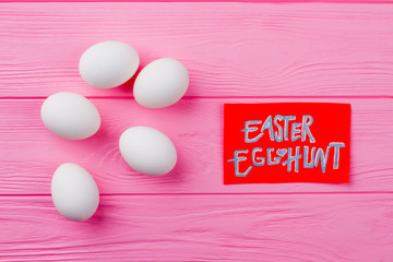 White chicken eggs on wooden background. Group of Easter eggs on pink wood. Easter egg hunt concept.