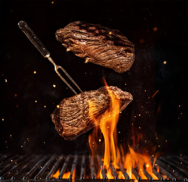 Flying beef steaks over grill grid, isolated on black background