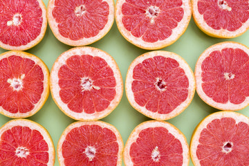 Background of grapefruit split in half on a green background