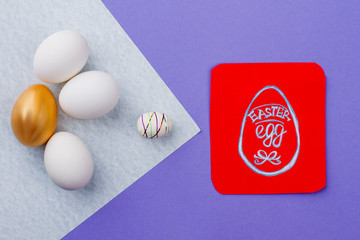 Easter composition with eggs and card. Red paper card with picture of Egg drawn by child. Golden egg among white eggs. Concept of happy Easter.