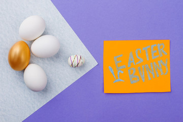 Easter composition on purple background. Golden egg, white eggs and styrofoam egg on paper sheet. Card with text Easter bunny.