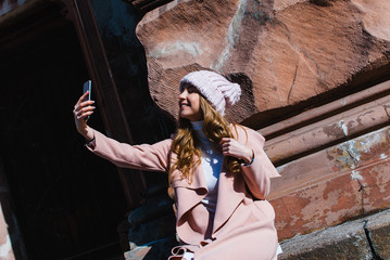 Winter selfie. Beautiful young woman in pink coat making selfie with smile while standing outdoors